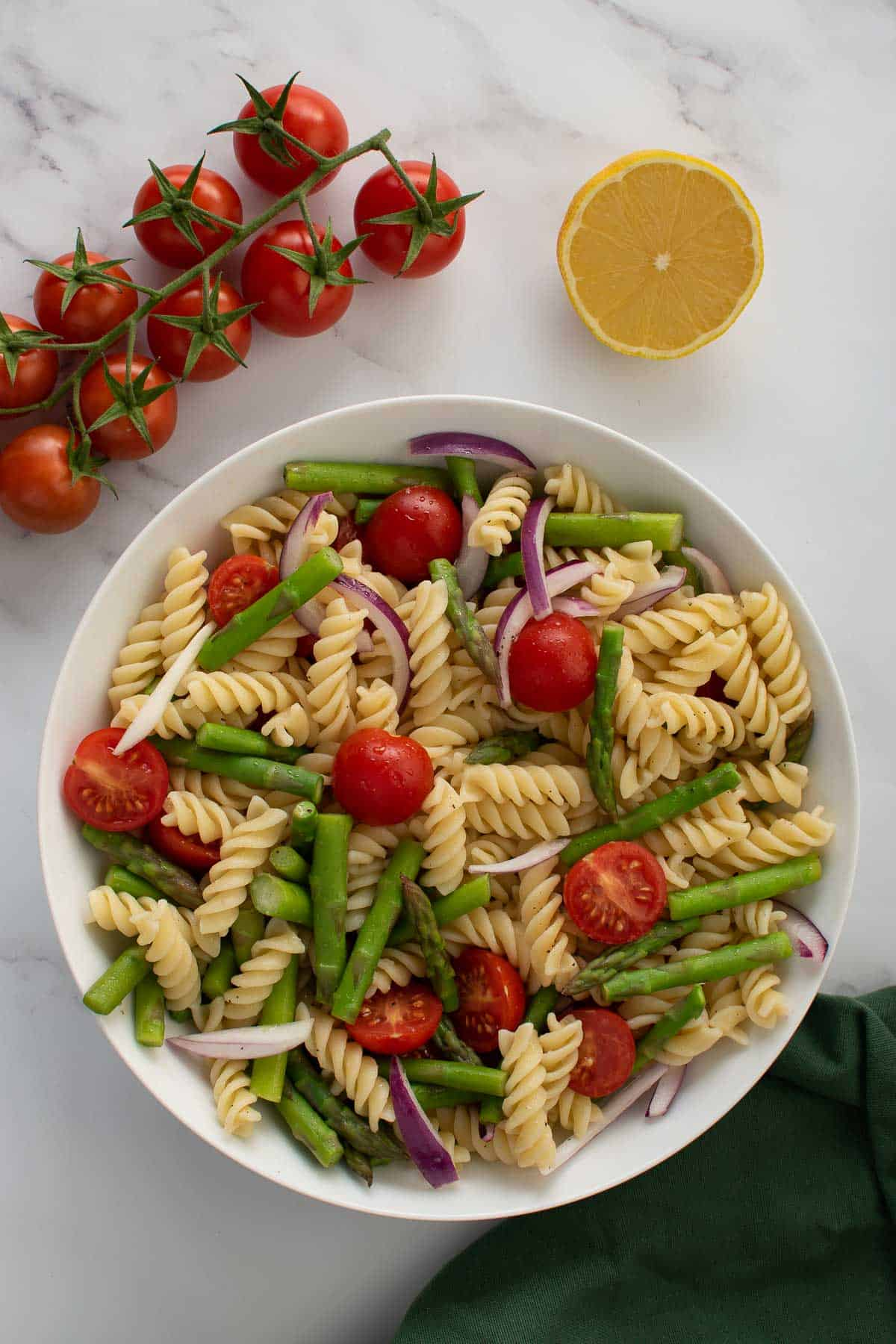 Pasta salad with asparagus and tomatoes in a bowl.