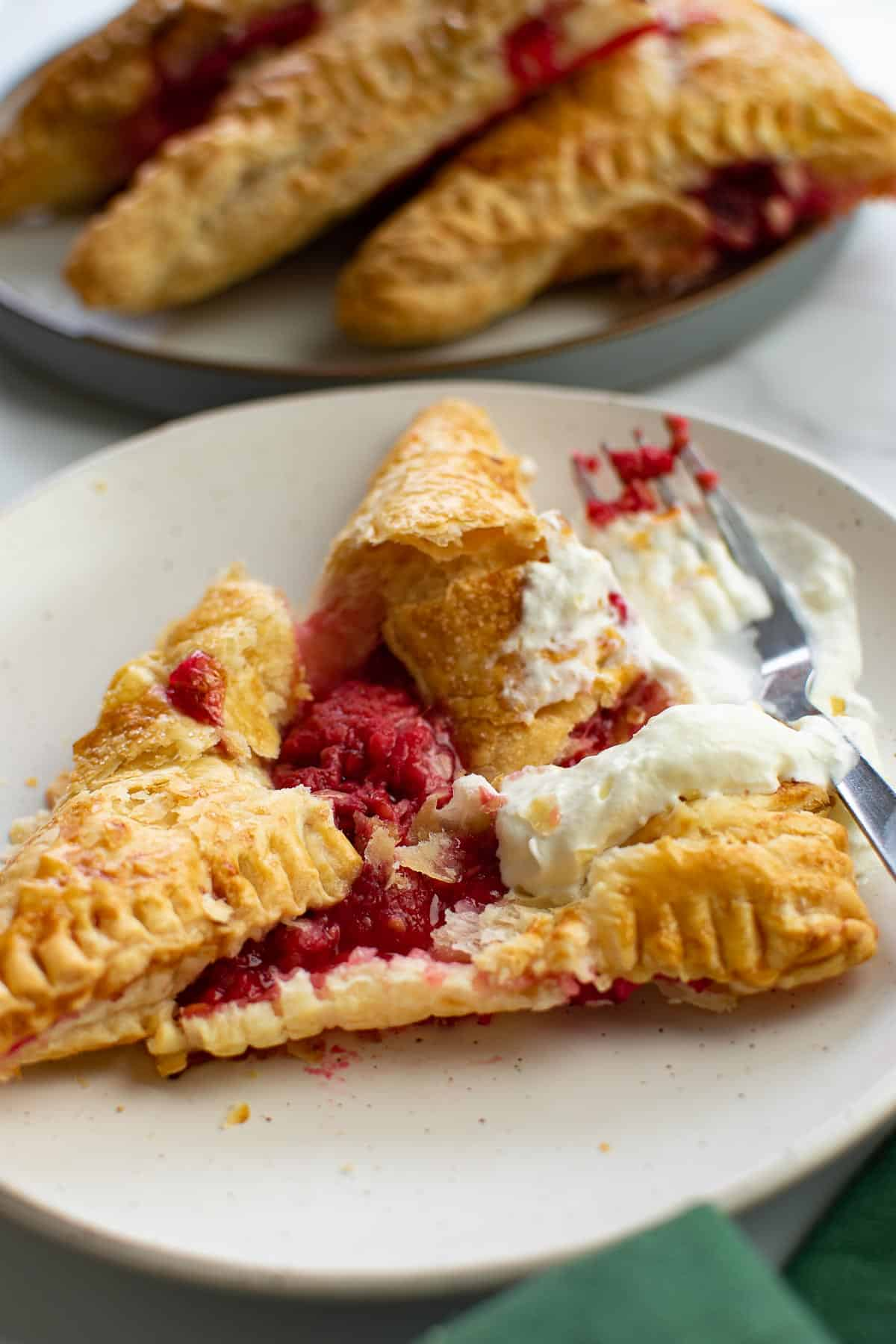 Served raspberry turnovers on plates.