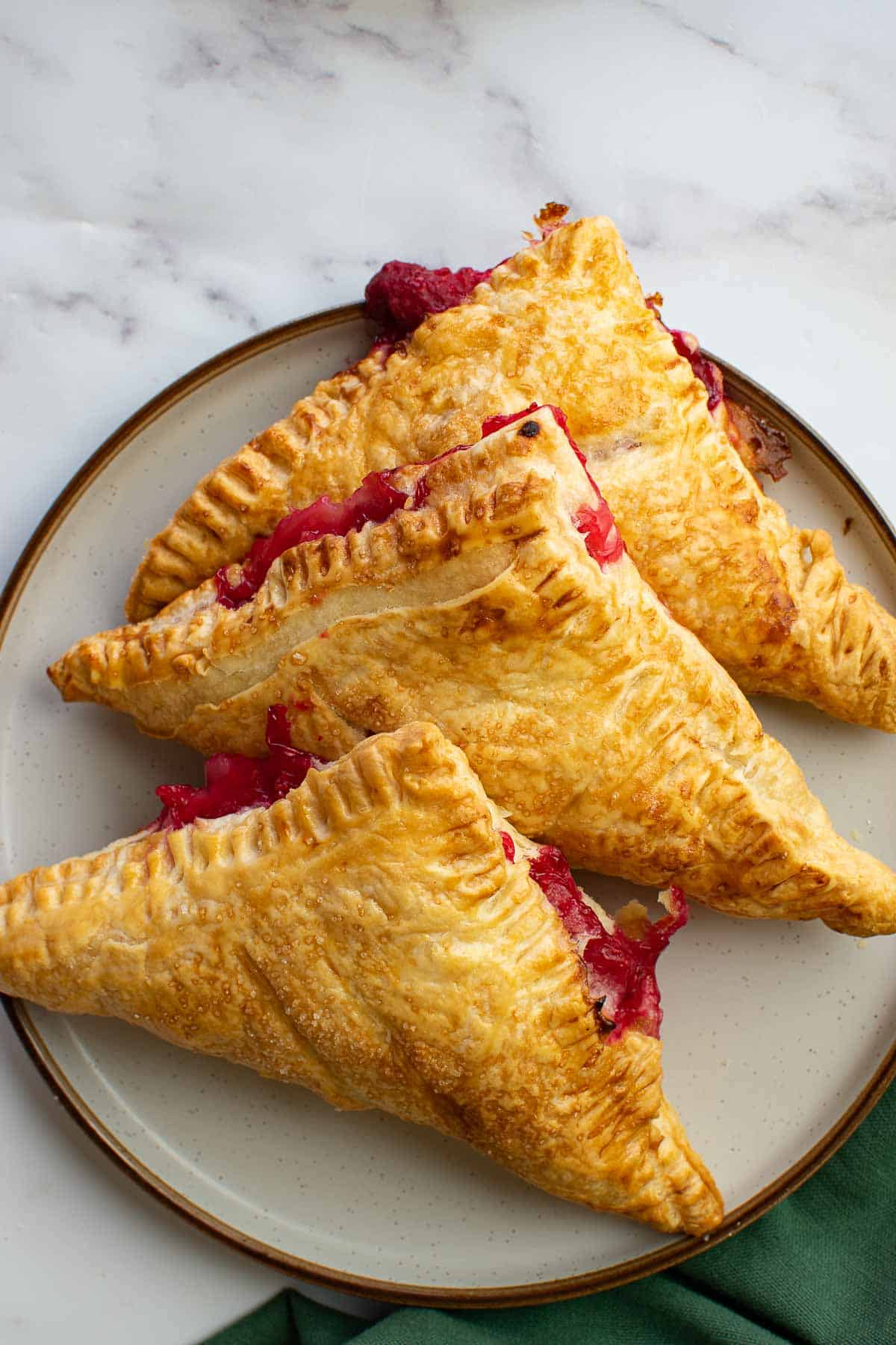 A plate with several raspberry hand pies.