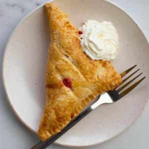 A raspberry turnover on a plate with whipped cream and a fork.