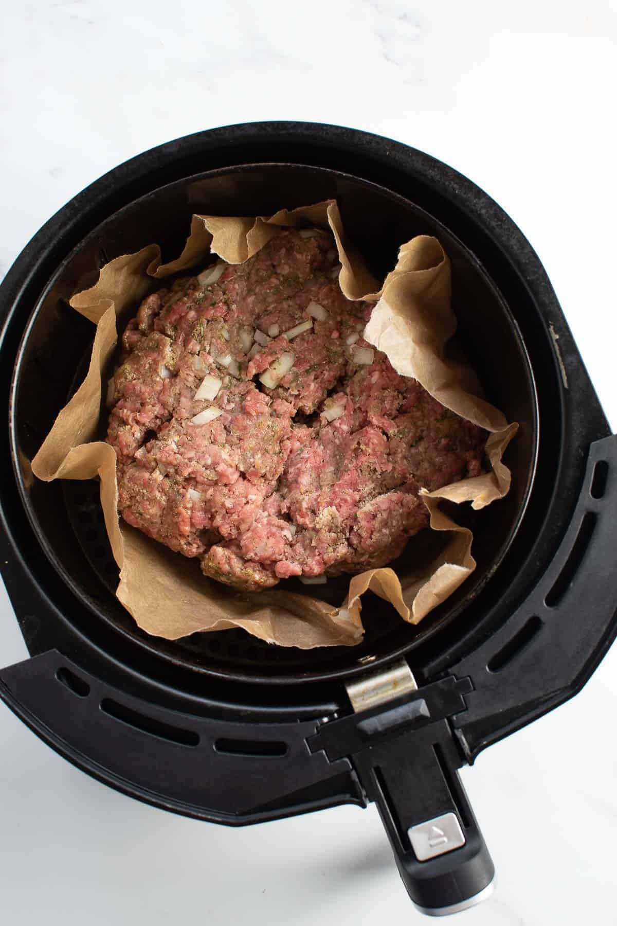 Raw meatloaf in an air fryer.