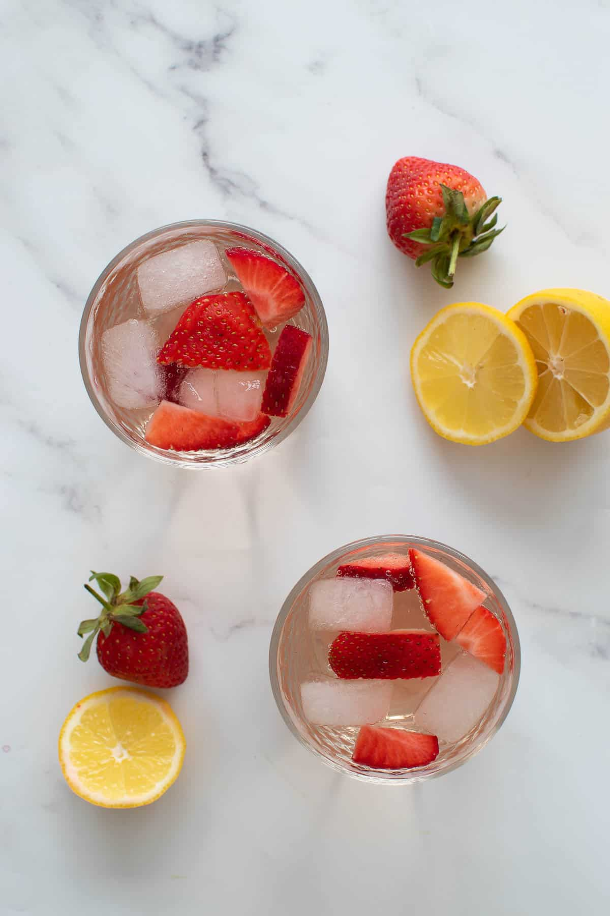 Two glasses of rose wine spritzer with strawberries and lemon.