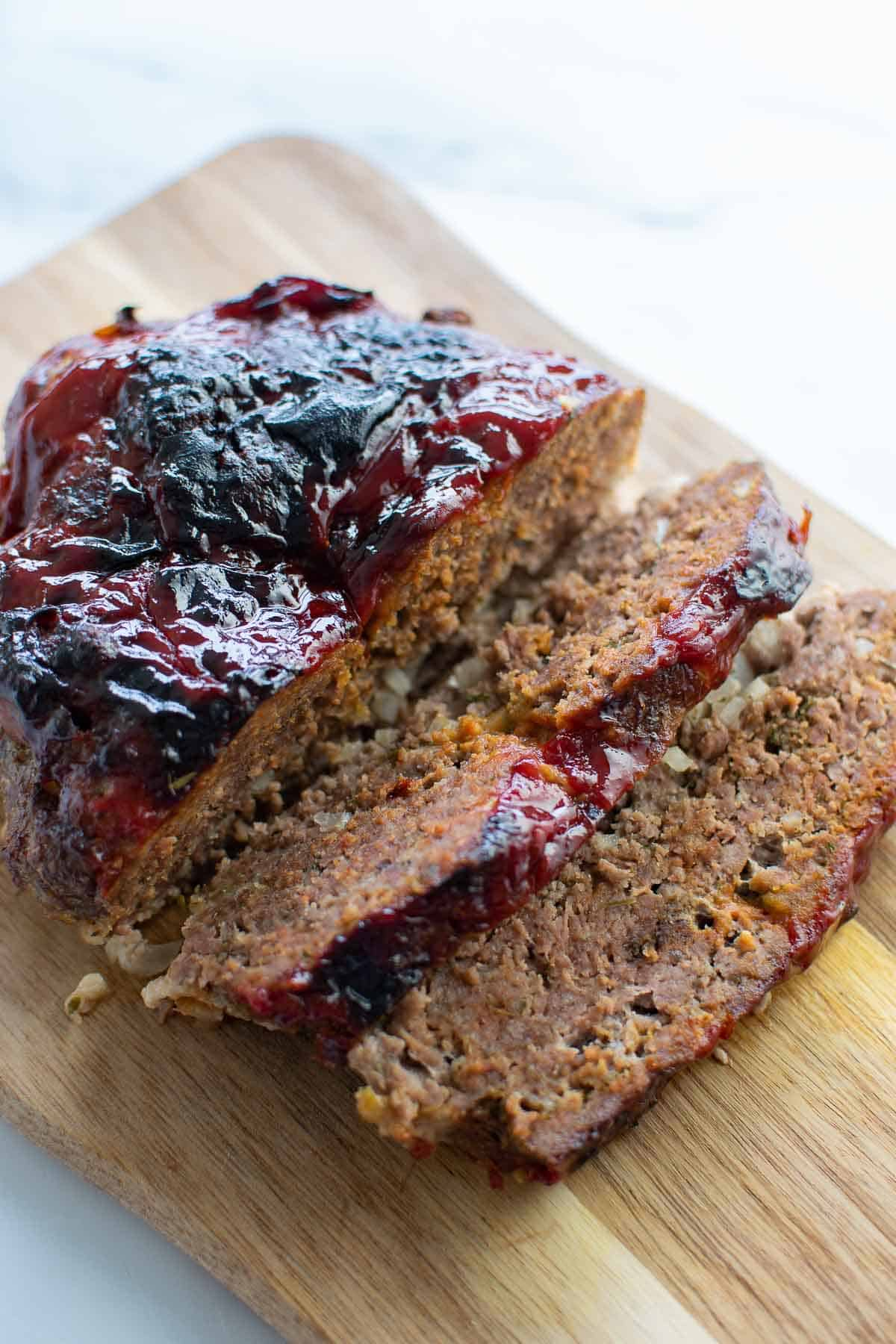 Sliced air fried meatloaf on a wooden board.