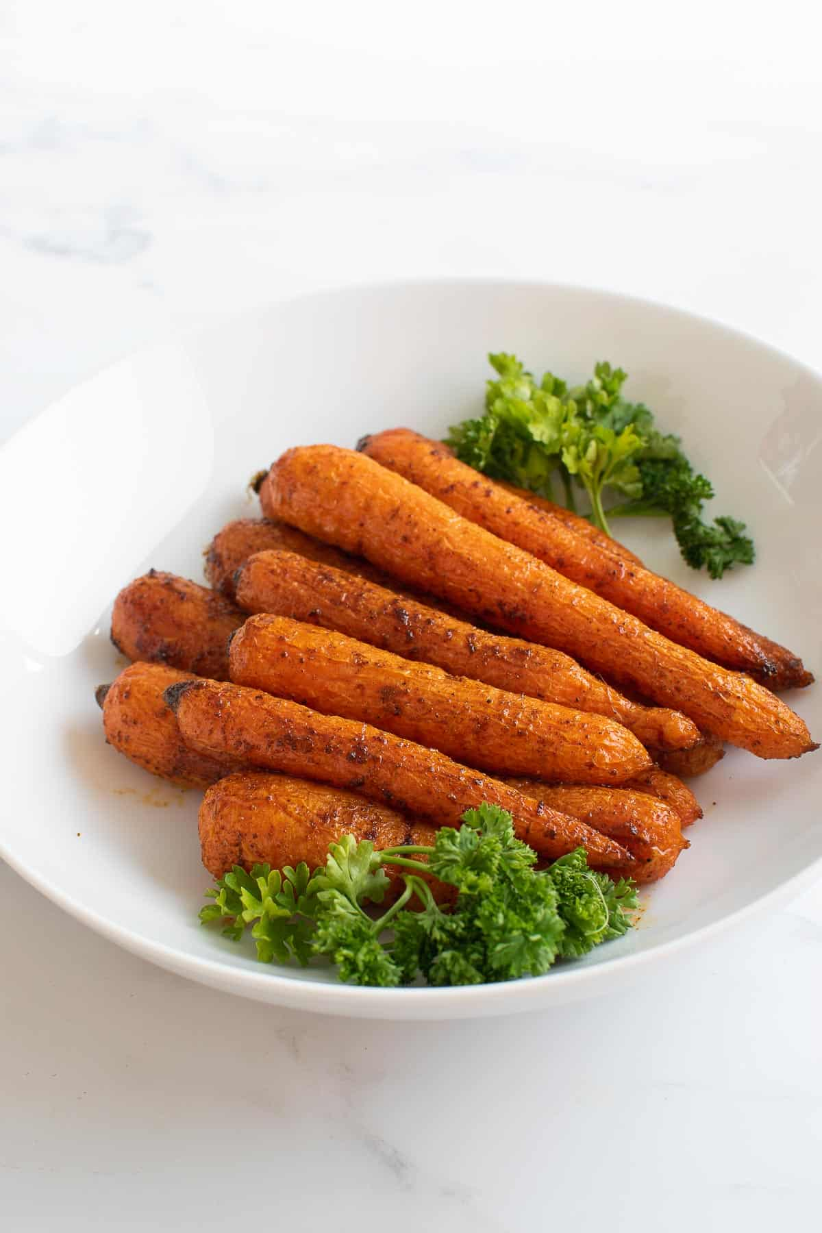 Spicy roast carrots with parsley in a bowl.