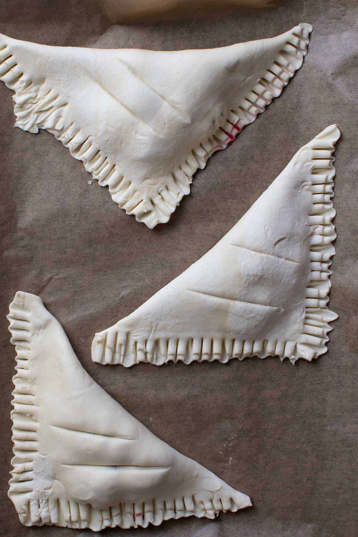 Uncooked turnovers on a baking sheet.