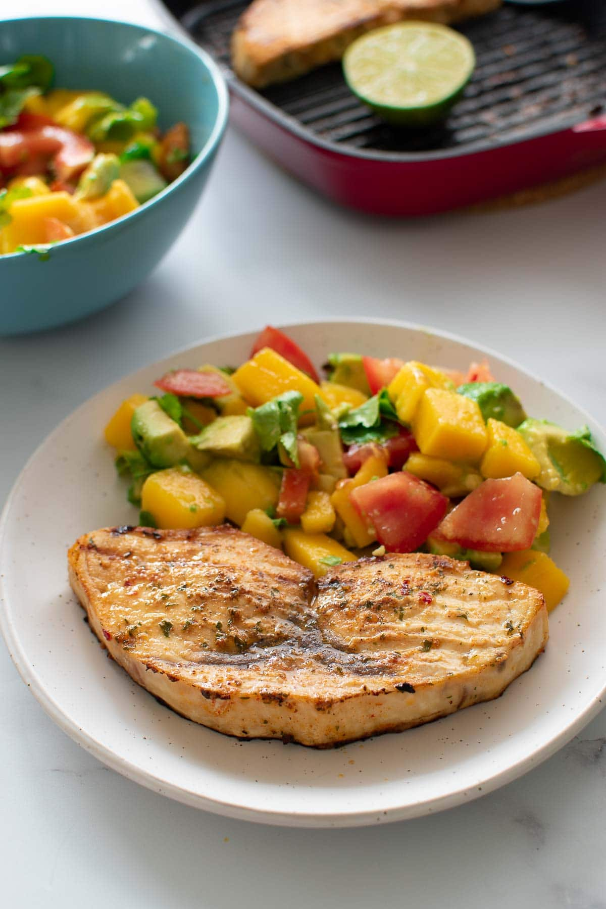 Swordfish served with salad, with a baking dish in the background.