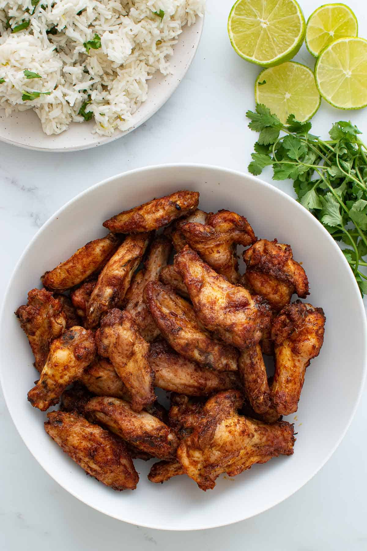 A bowl of Cajun chicken wings, with rice, lime and cilantro on the side.