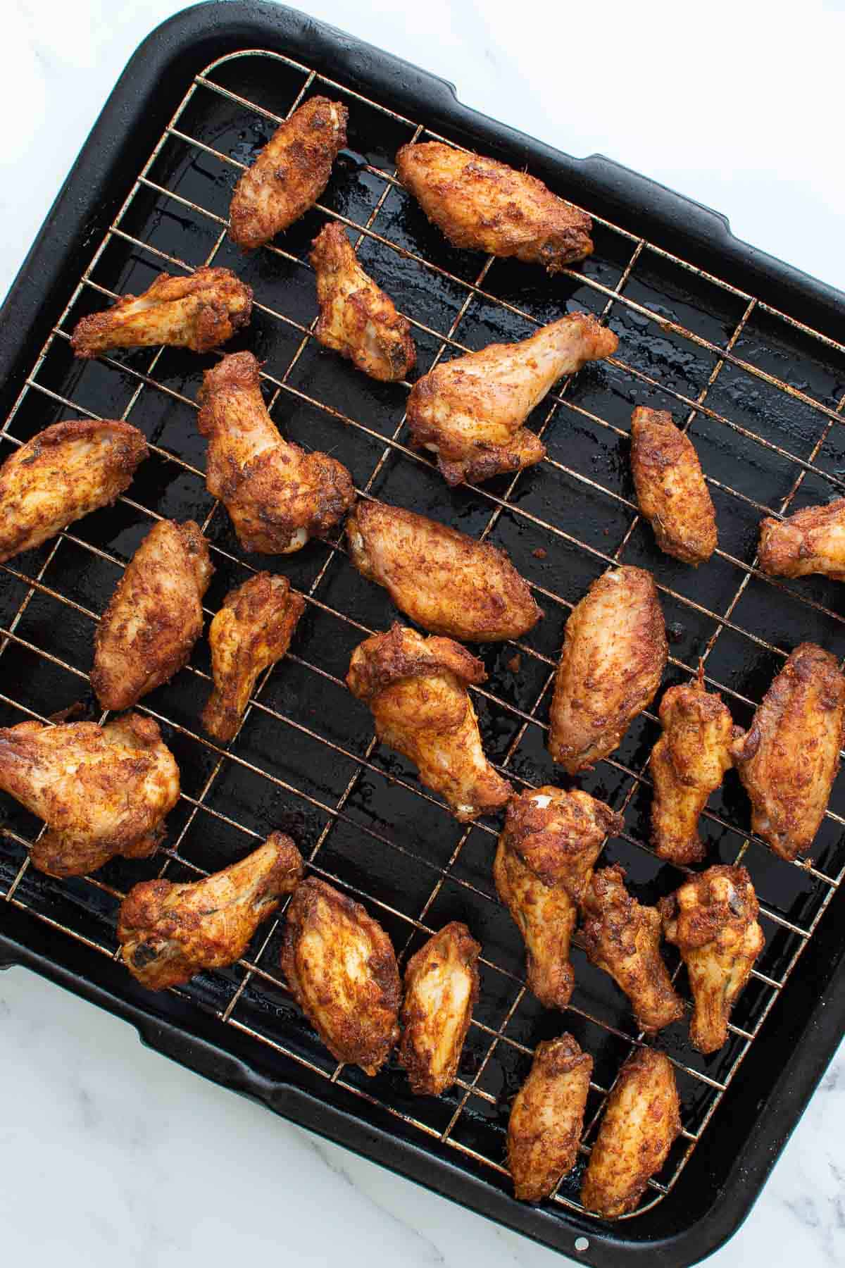 Chicken wings on a wire rack.