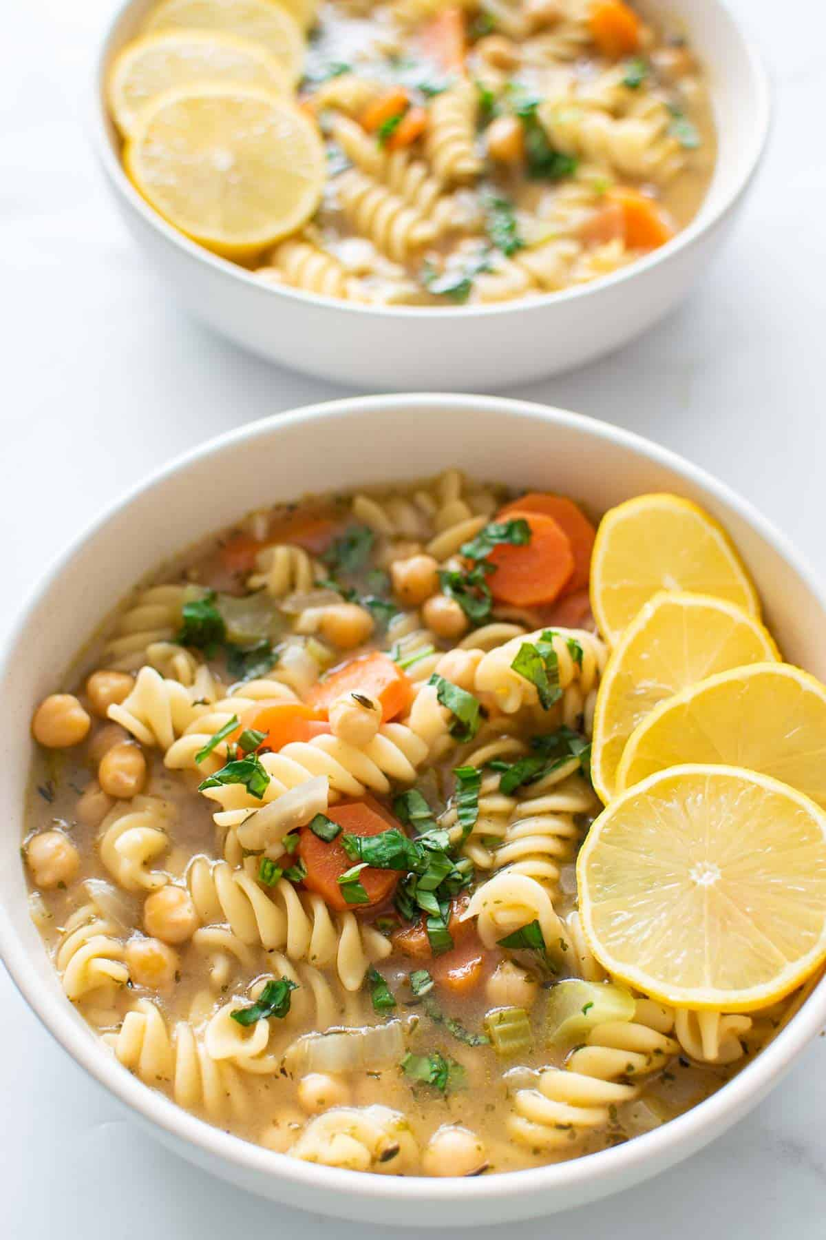Two bowls of vegetarian soup with chickpeas, noodles and carrots.