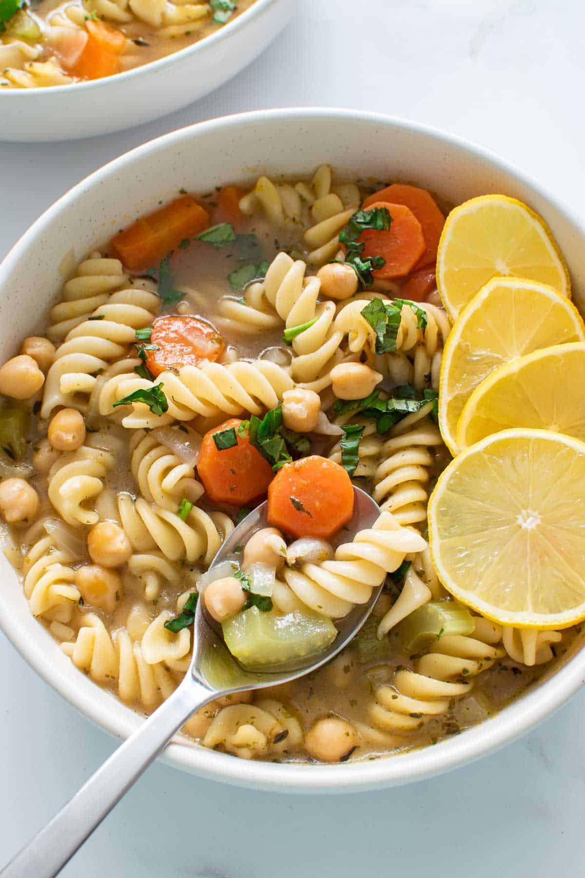 Chickpea pasta soup, with a spoon lifting up a serving.