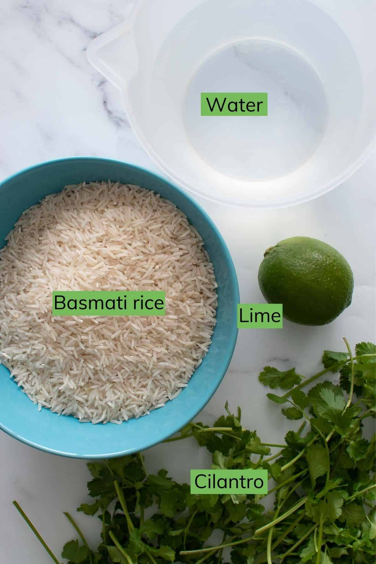 Rice, water, cilantro and lime laid out on a table.