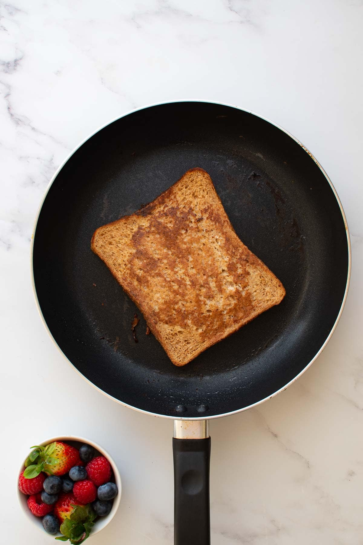 French toast being cooked in a skillet.