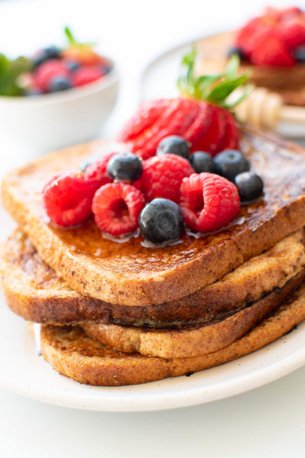 Close up of a stack of French toast with raspberries and blueberries.