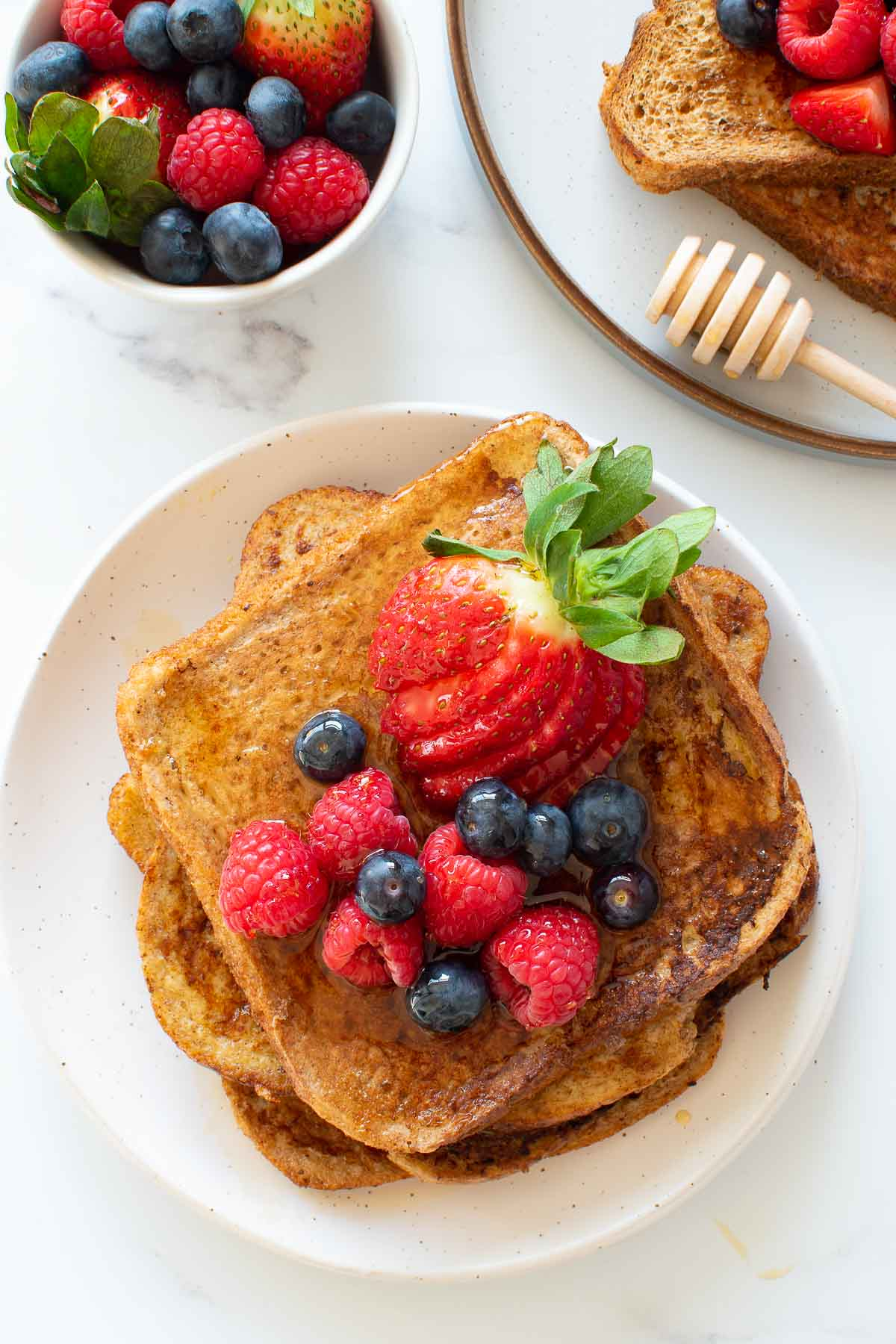 A stack of wholemeal French toast with strawberries.