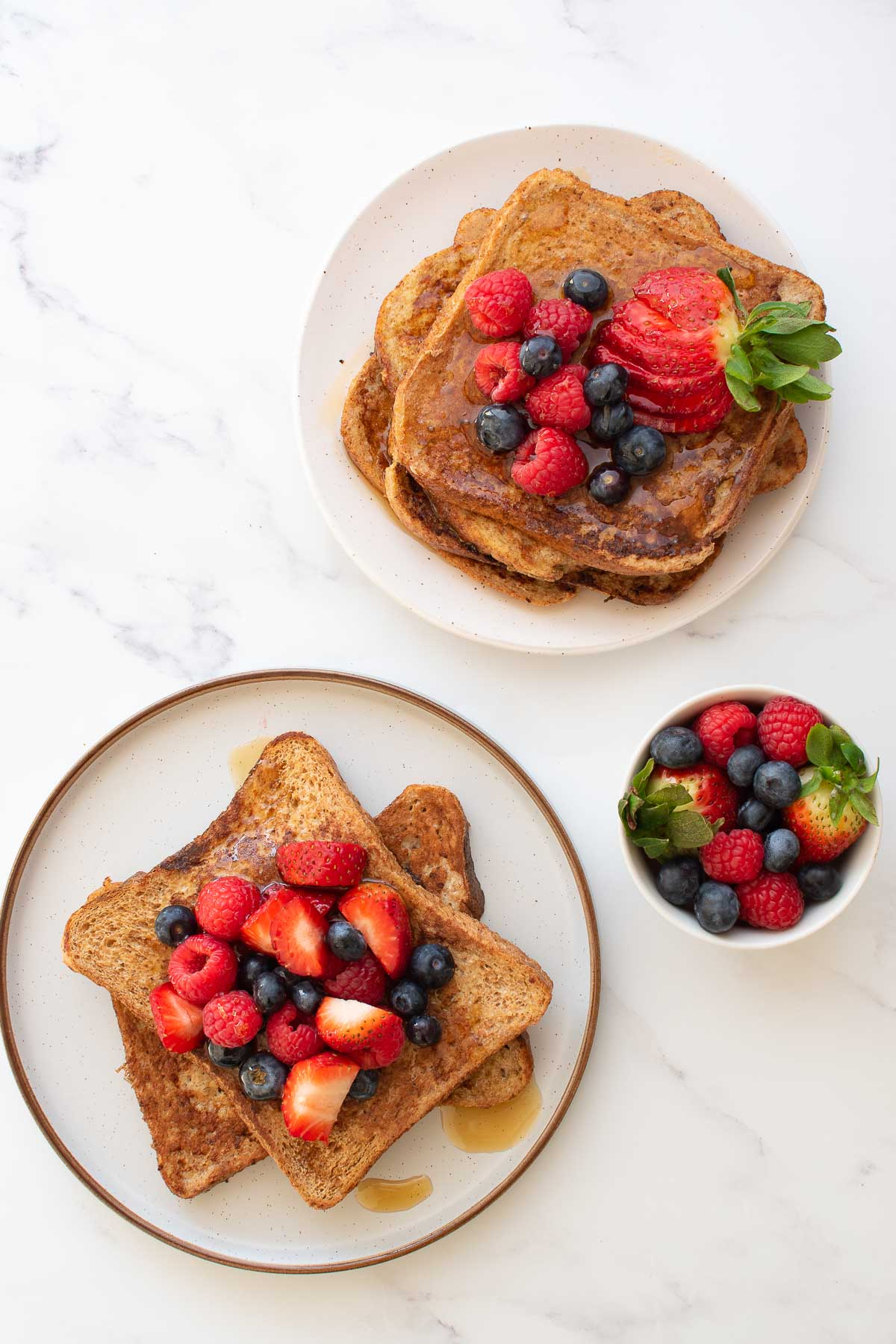 Two plates of French toast with berries.