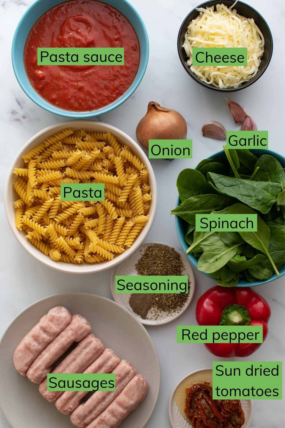 Ingredients needed to make Sausage Pasta Bake laid out on a table.