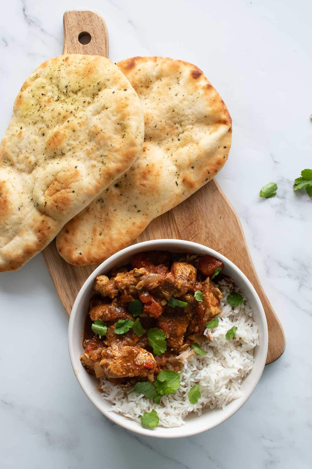 A bowl of chicken curry with naan on the side.