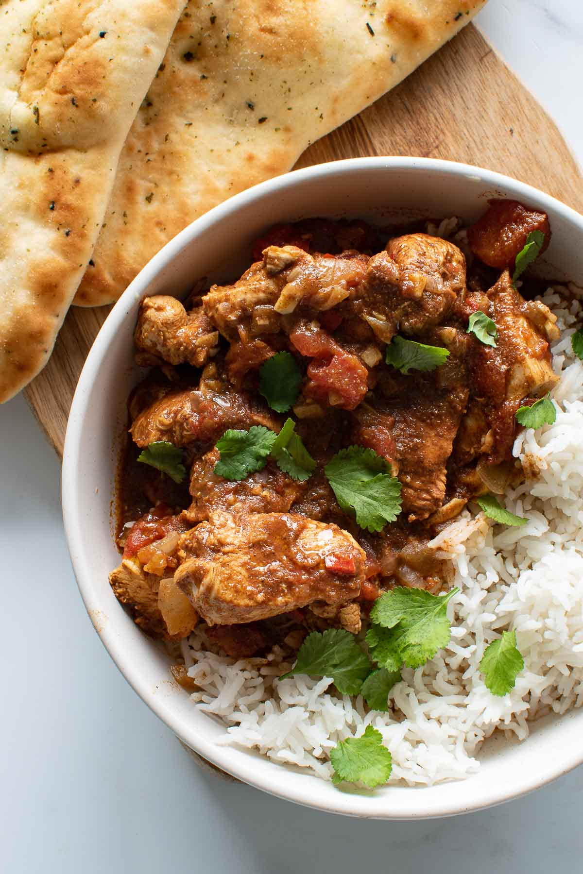 Chicken curry and rice in a bowl, with naan in the background.