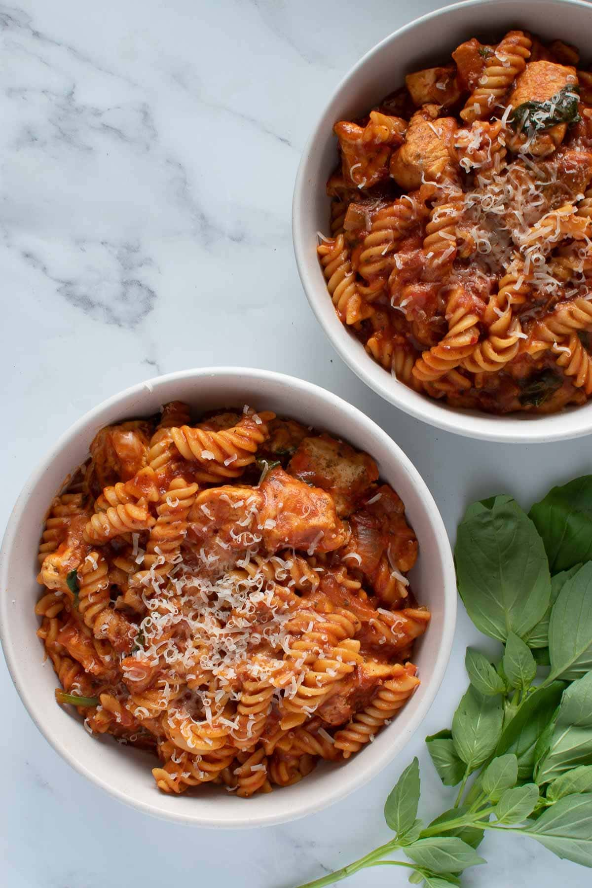Two bowls of pasta with chicken.