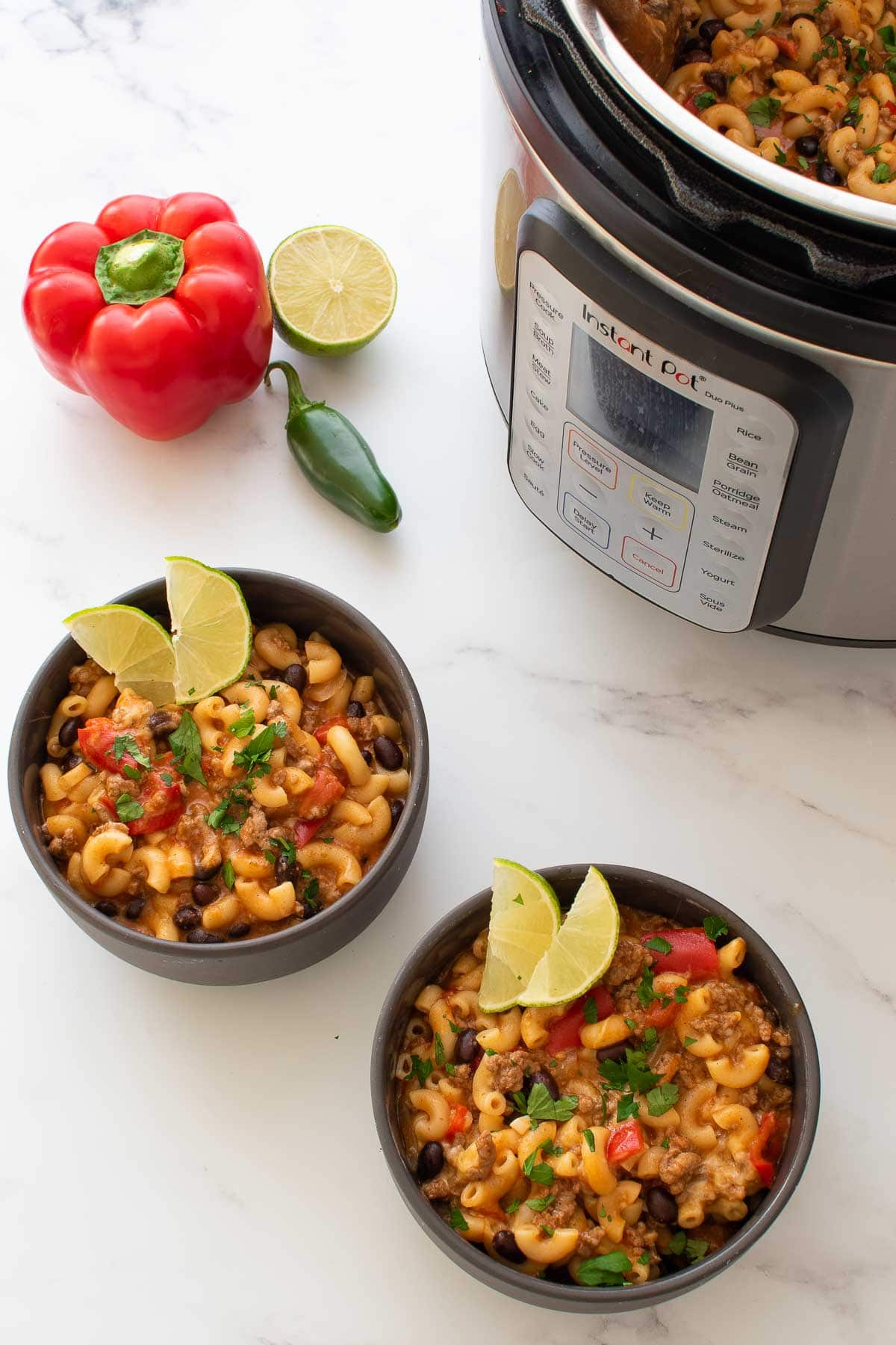 Two bowls of chili mac, with vegetables on the side and a pressure cooker in the background.