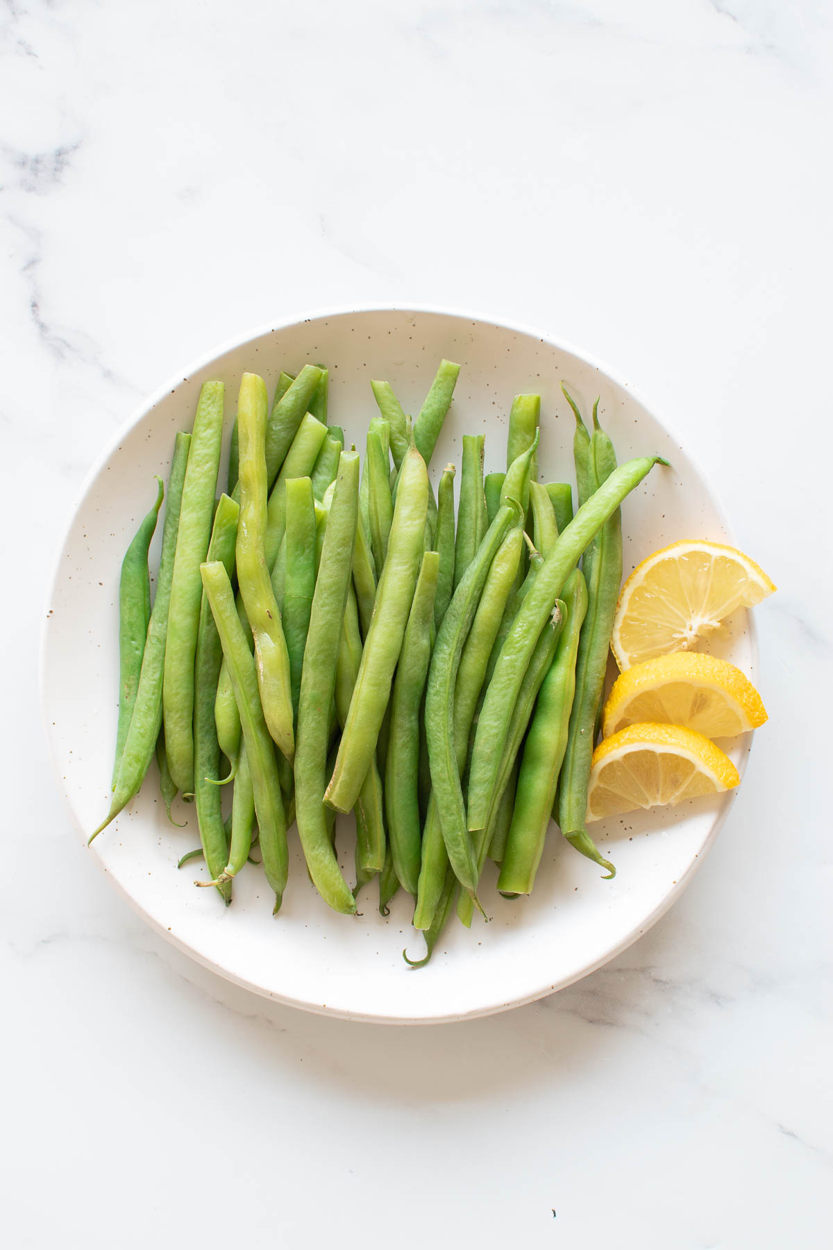 A plate of steamed green beans with lemon wedges.