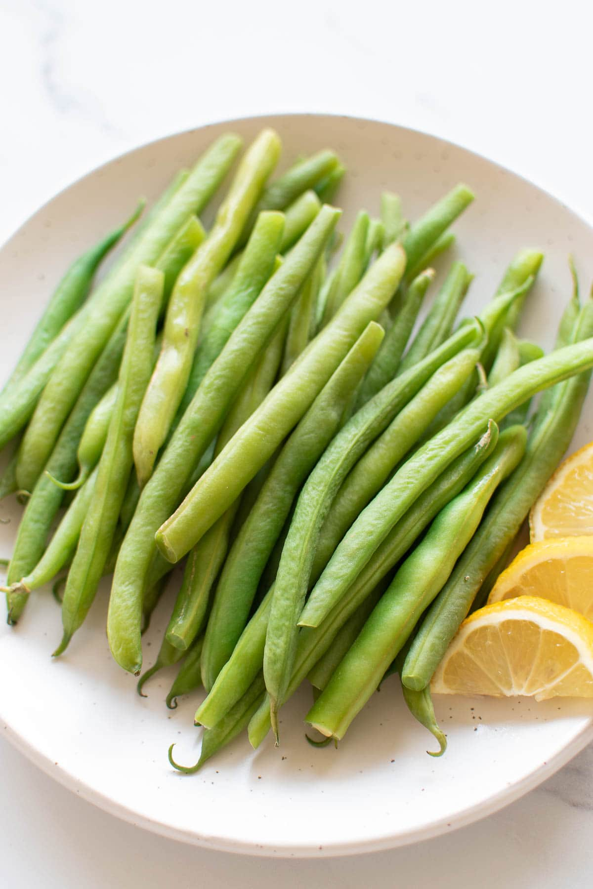 Close up of a plate of steamed green beans.