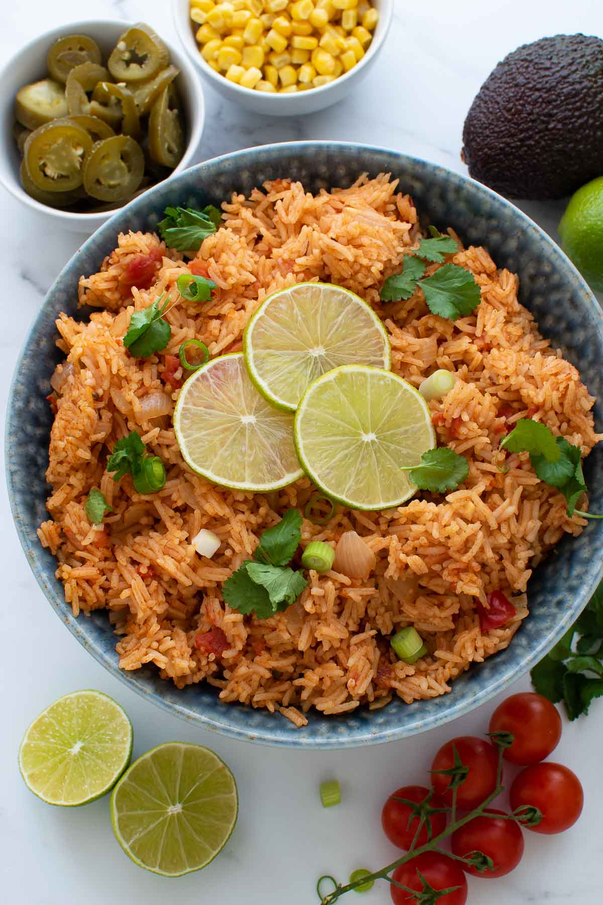 Mexican rice in a bowl, surrounded by sides and garnishes.