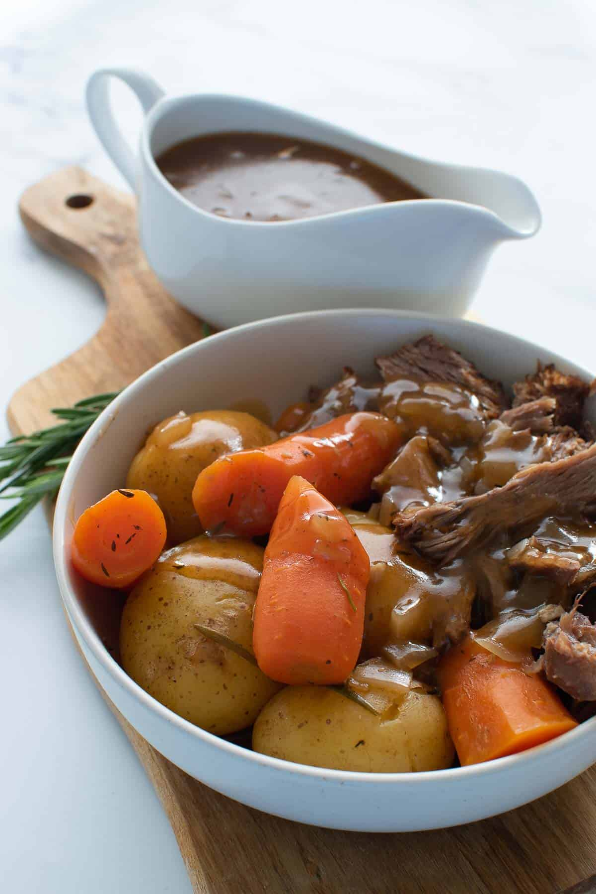 Beef, potatoes and carrots with gravy in a bowl.
