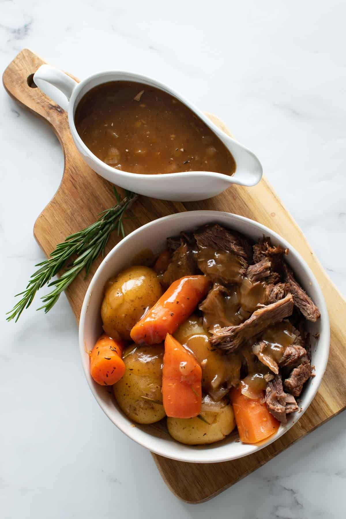 Pressure cooked pot roast and gravy on a wooden board.