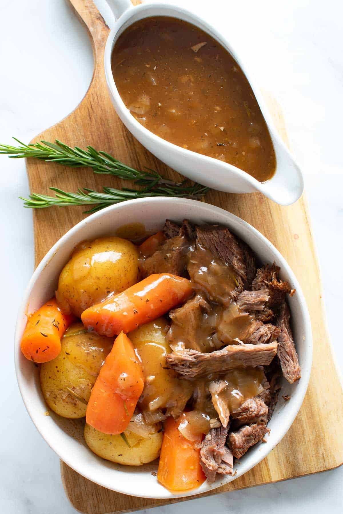 A bowl of instant pot pot roast, with gravy on the side.