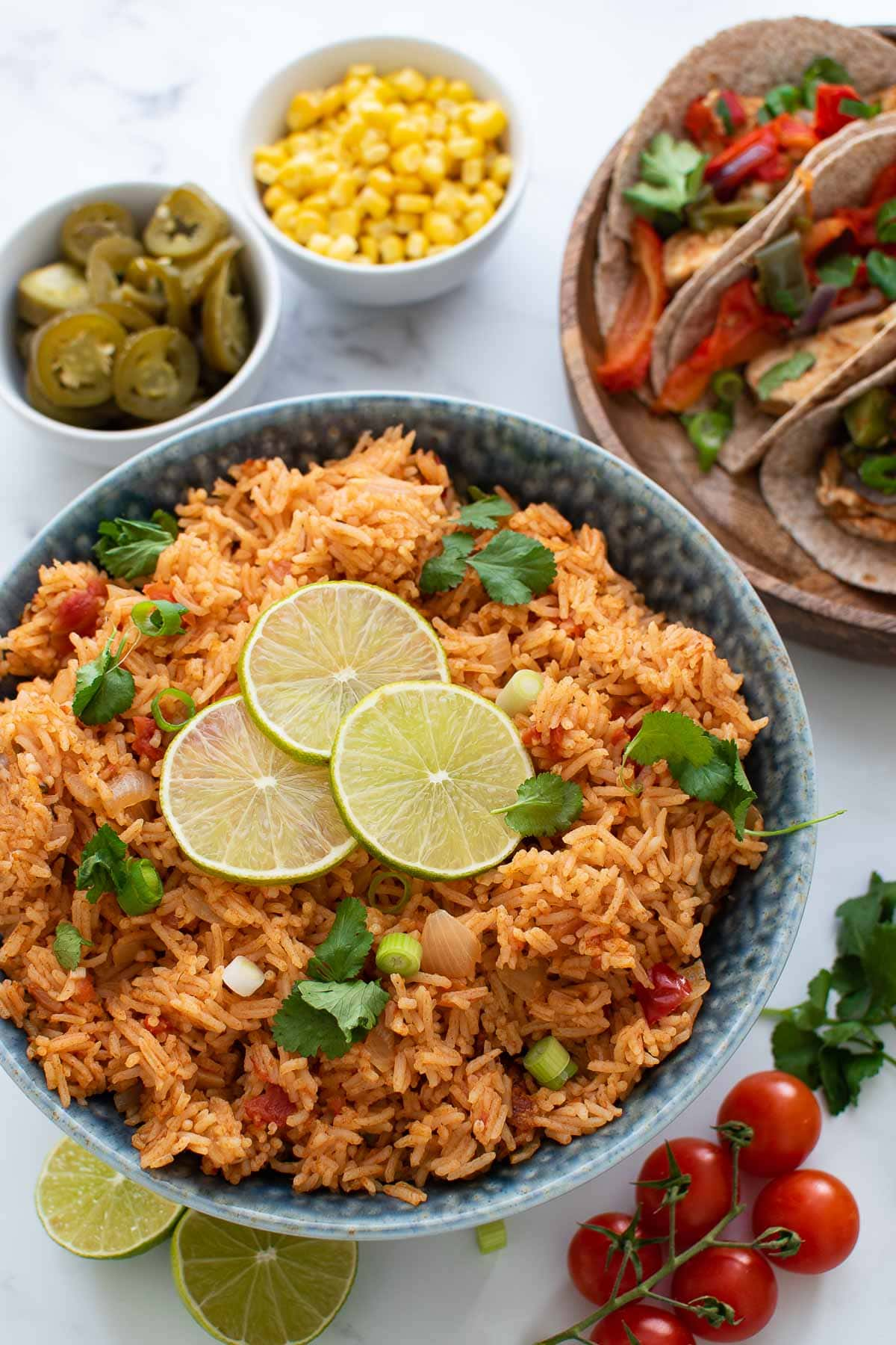 A bowl of Mexican rice garnished with lime and cilantro.