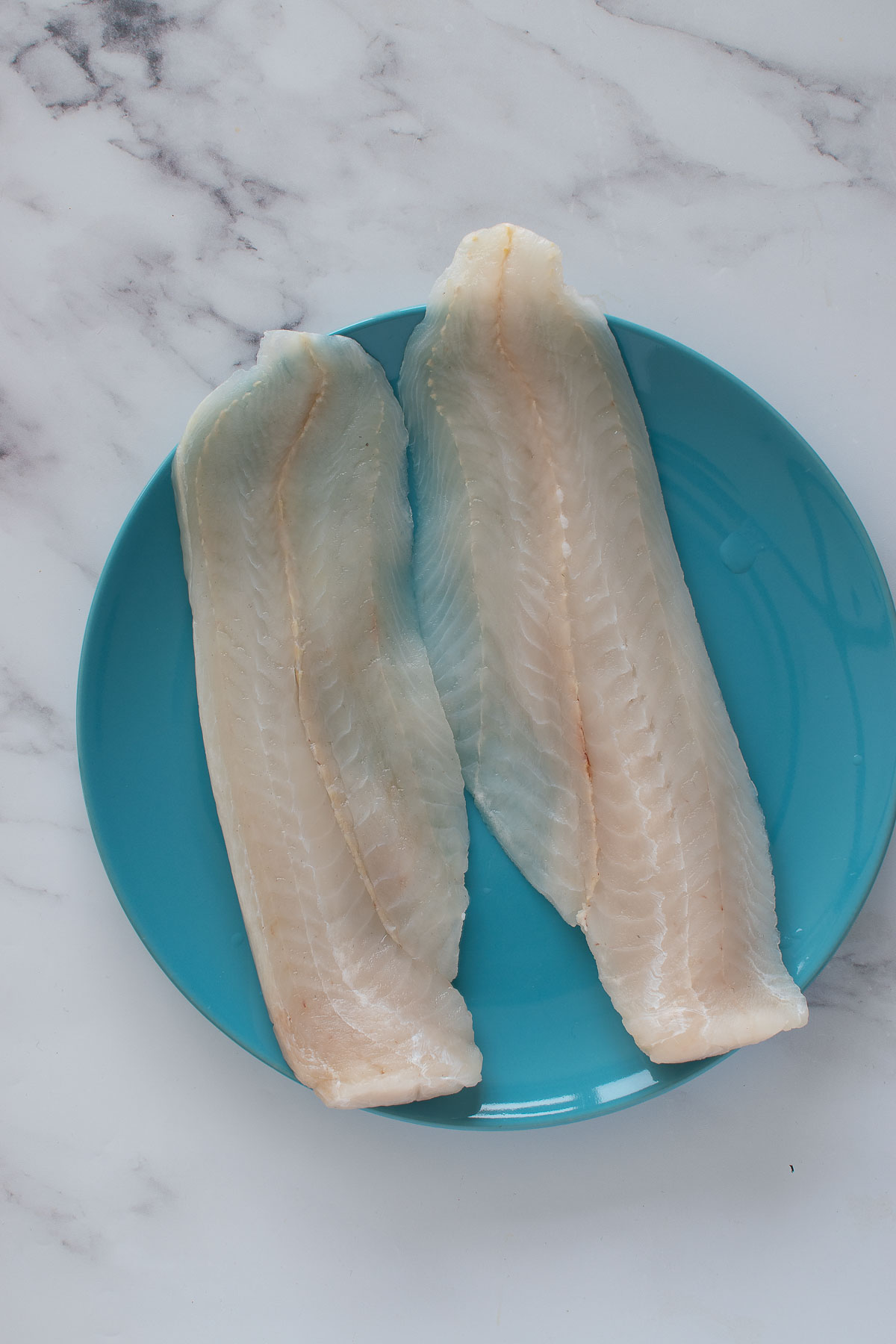Two hake fish fillets on a plate.
