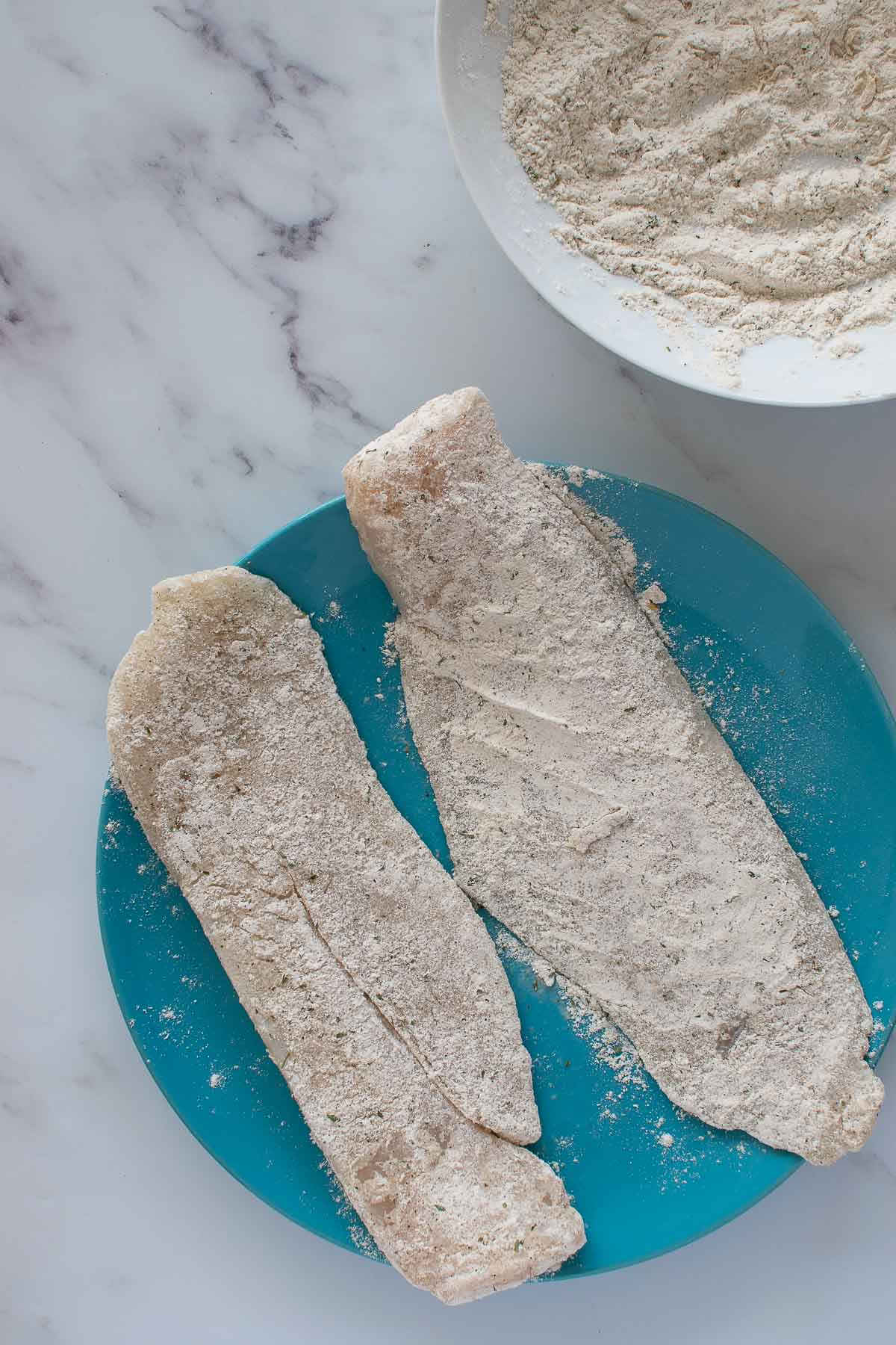 Hake fillets coated in flour and seasoning.