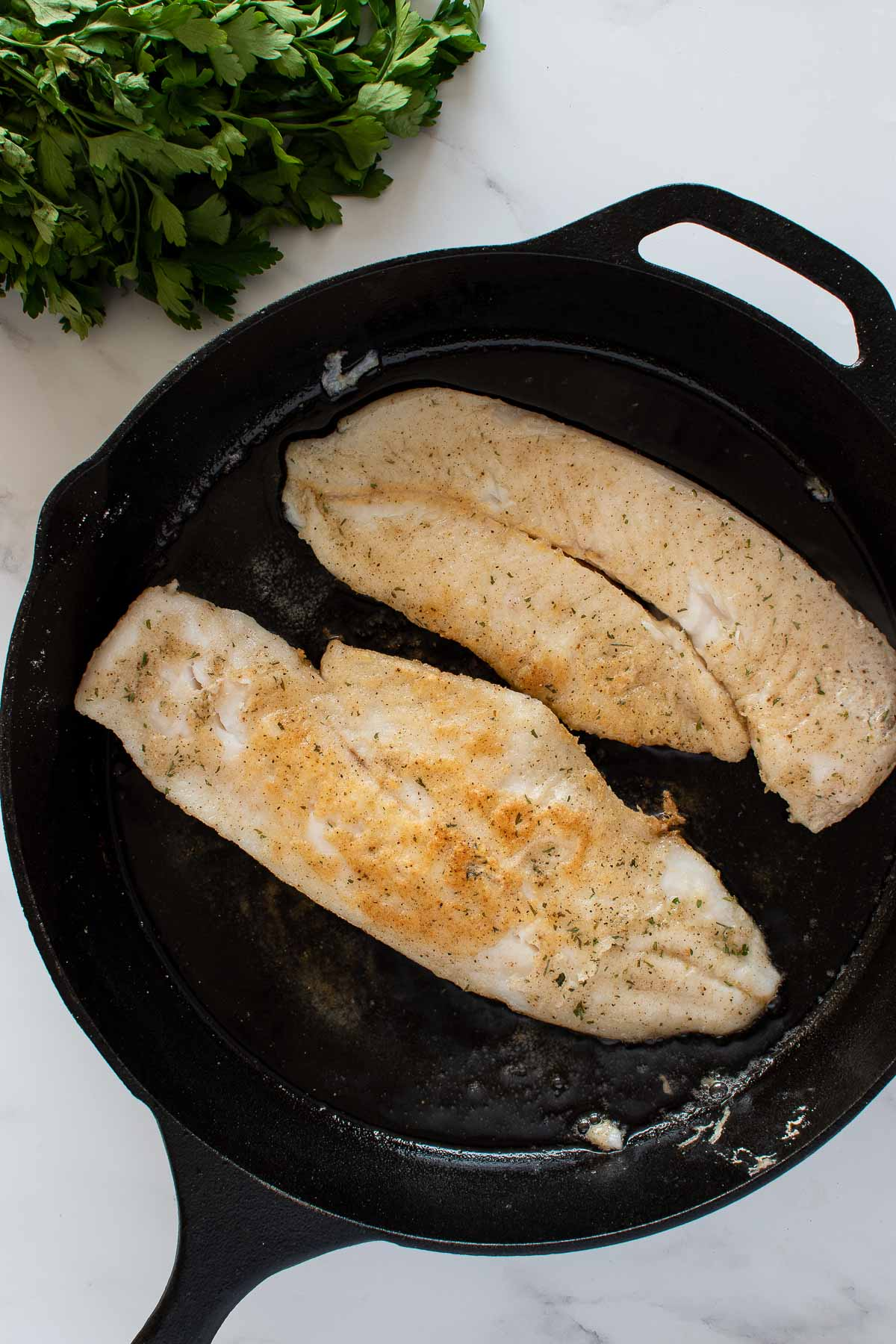 Pan seared hake in a cast iron skillet.