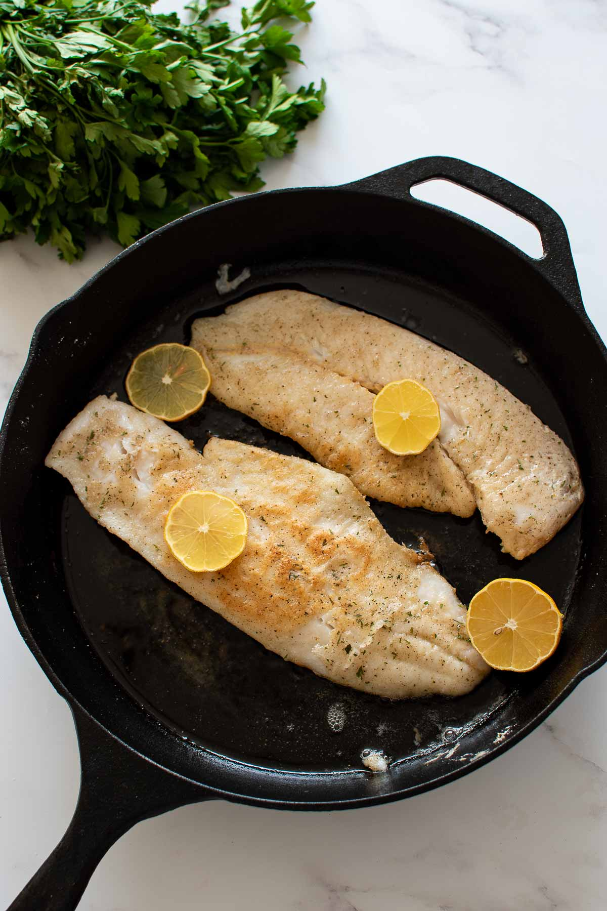 Pan fried hake with lemon slices in a cast iron pan.