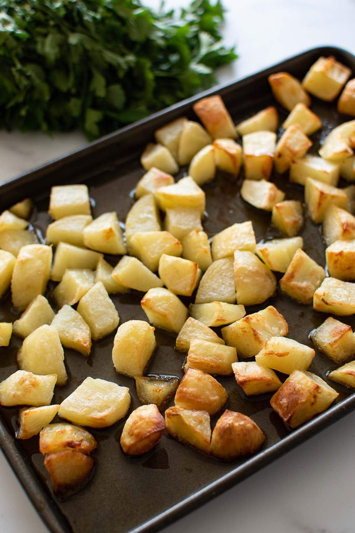 Parmentier potatoes cubed roast potatoes on a baking sheet.