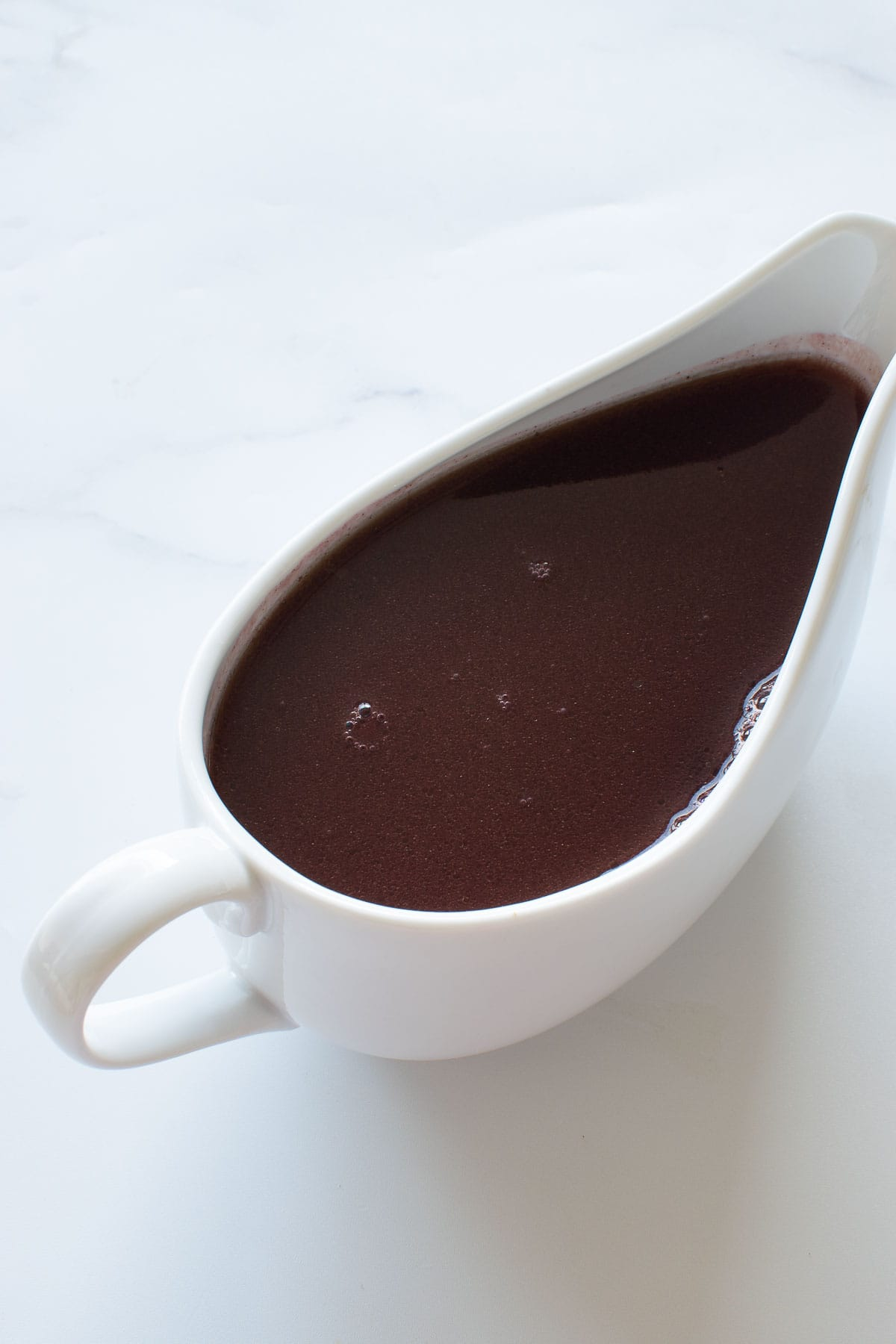 Close up of red wine jus in a jug.
