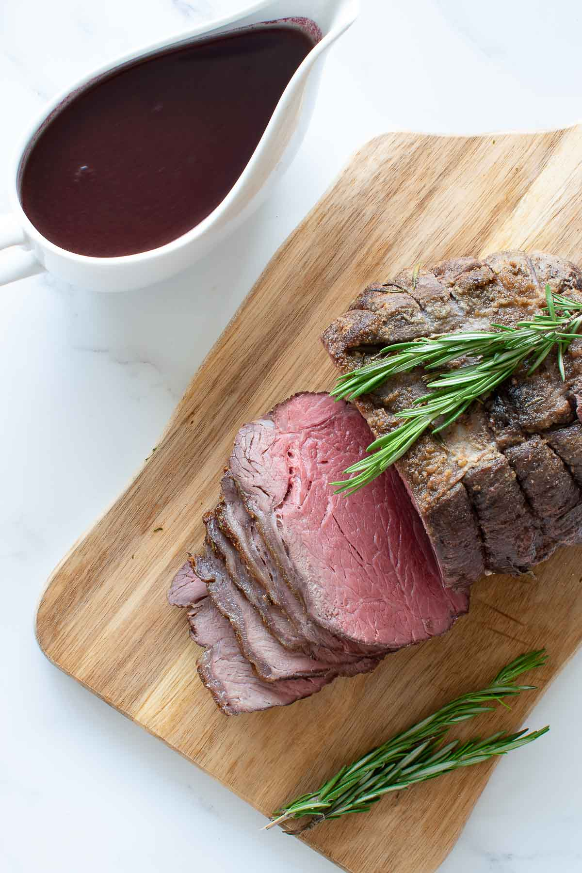Sliced roast beef with gravy on the side.