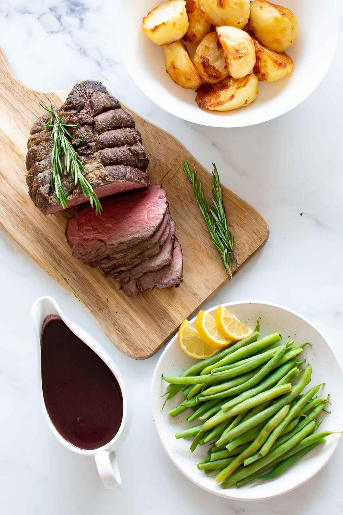 A table with roast beef, green beans, roast potatoes and red wine jus.