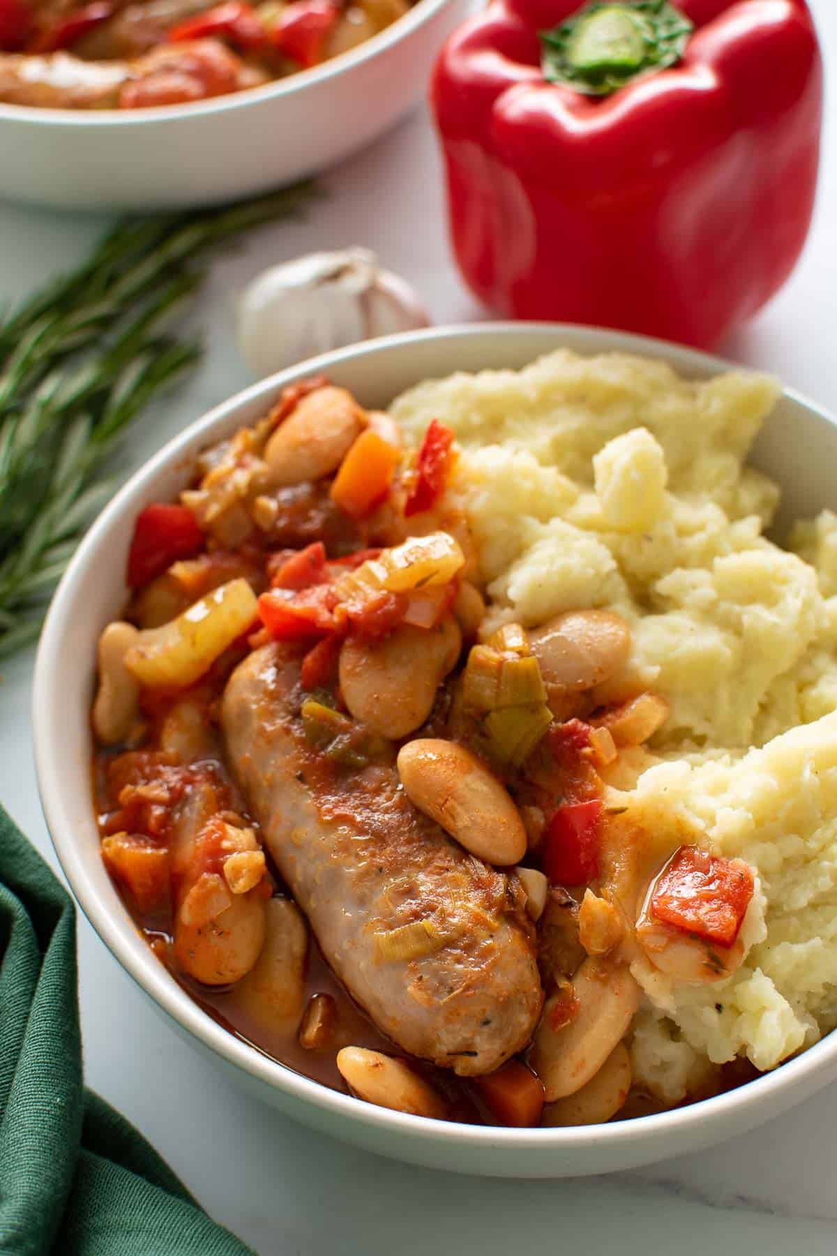 A bowl of sausage casserole and mashed potatoes.