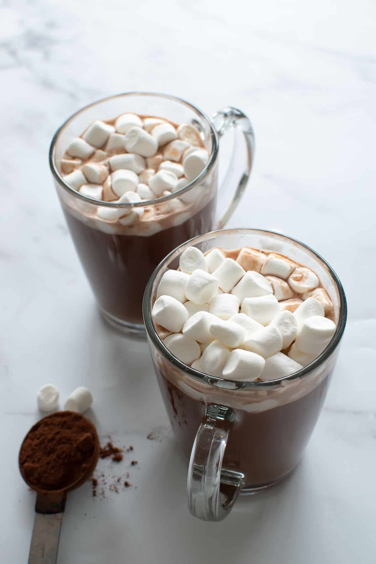 Two glasses of hot chocolate with marshmallows.