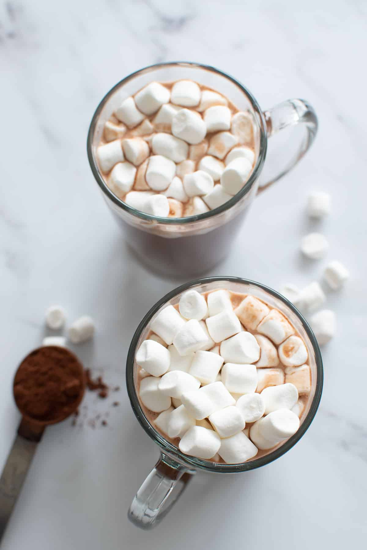Two cups of sugar free hot chocolate, with a spoon of cocoa powder on the side.