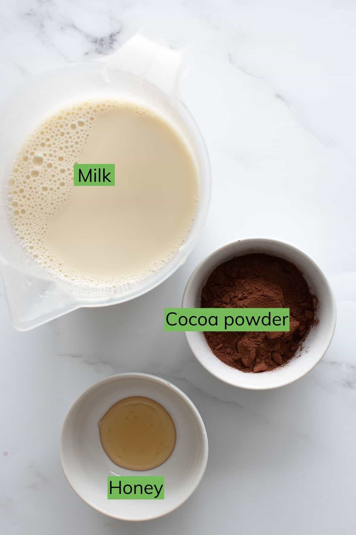 Cocoa powder, milk and honey laid out on a table.
