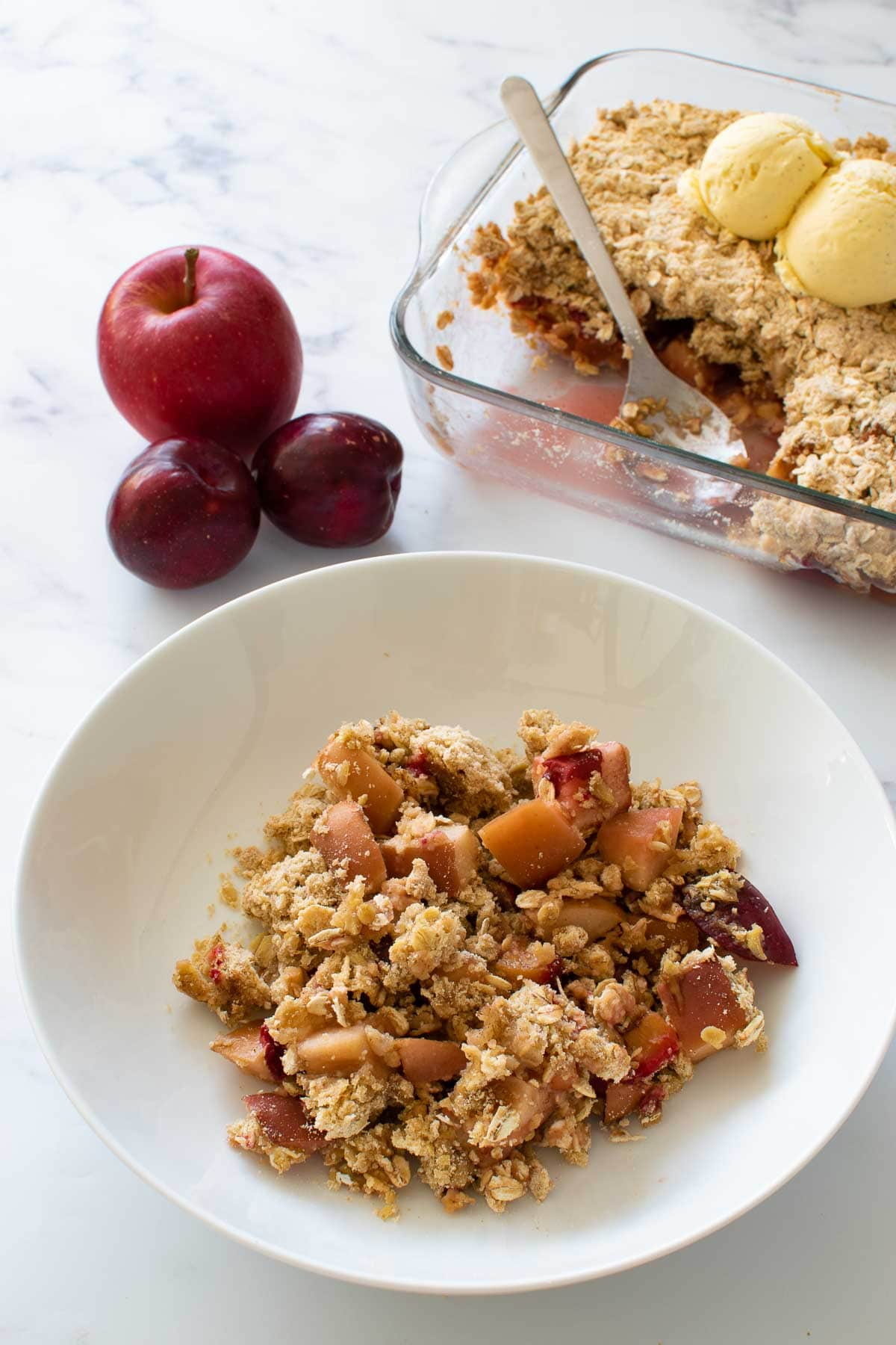 Apple crumble with plums in a bowl.