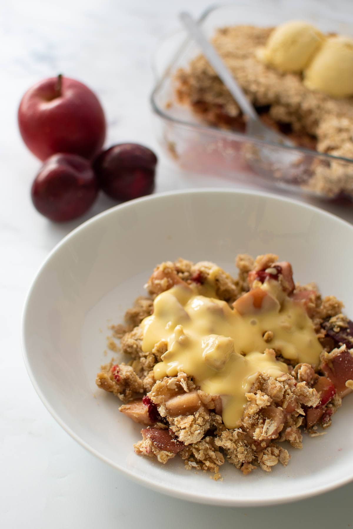 A plate with plum and apple crumble with custard.