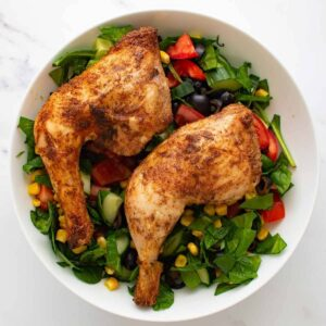 Baked chicken leg quarters with a mixed salad.