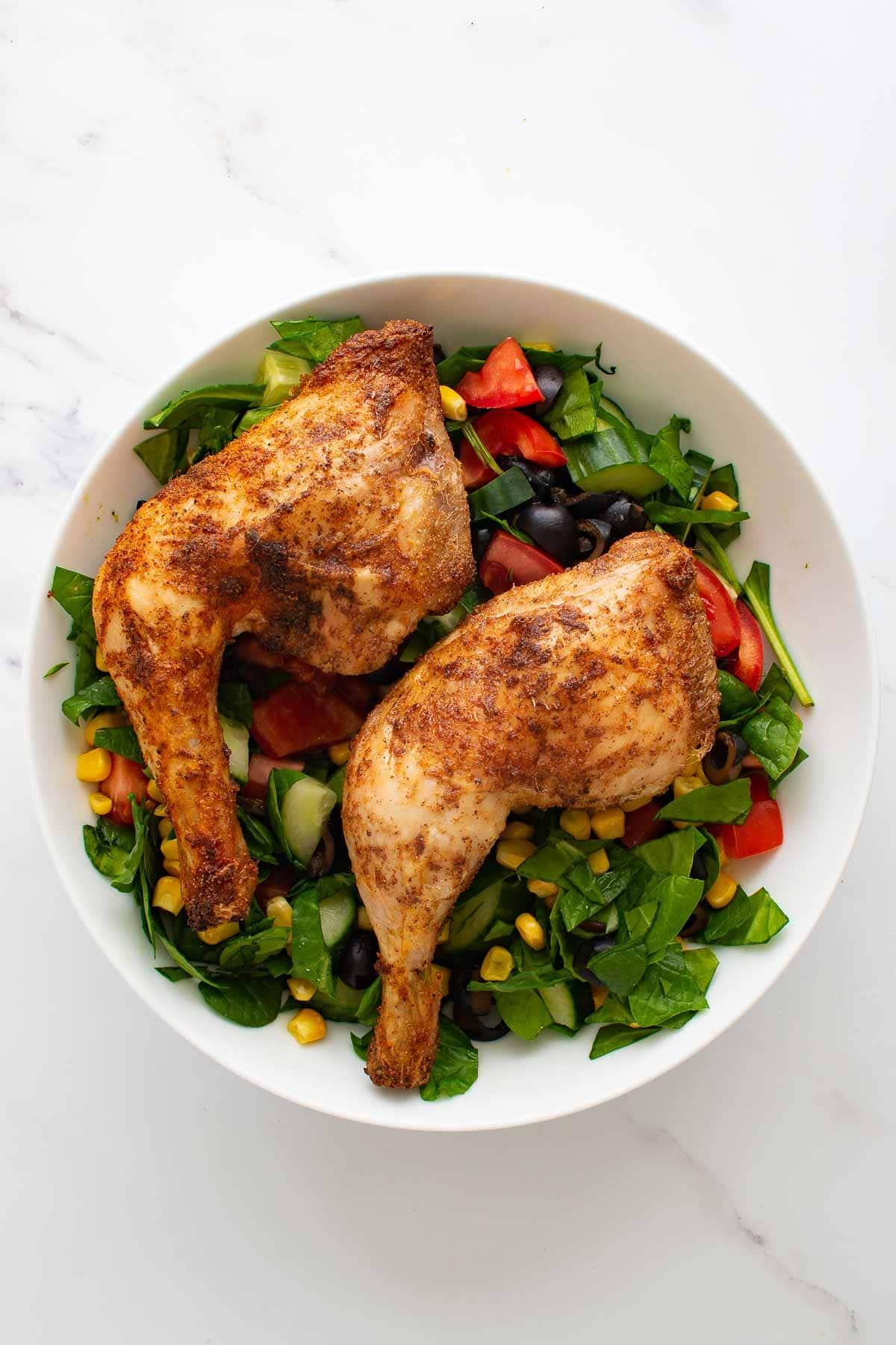 Crispy chicken leg quarters with salad.