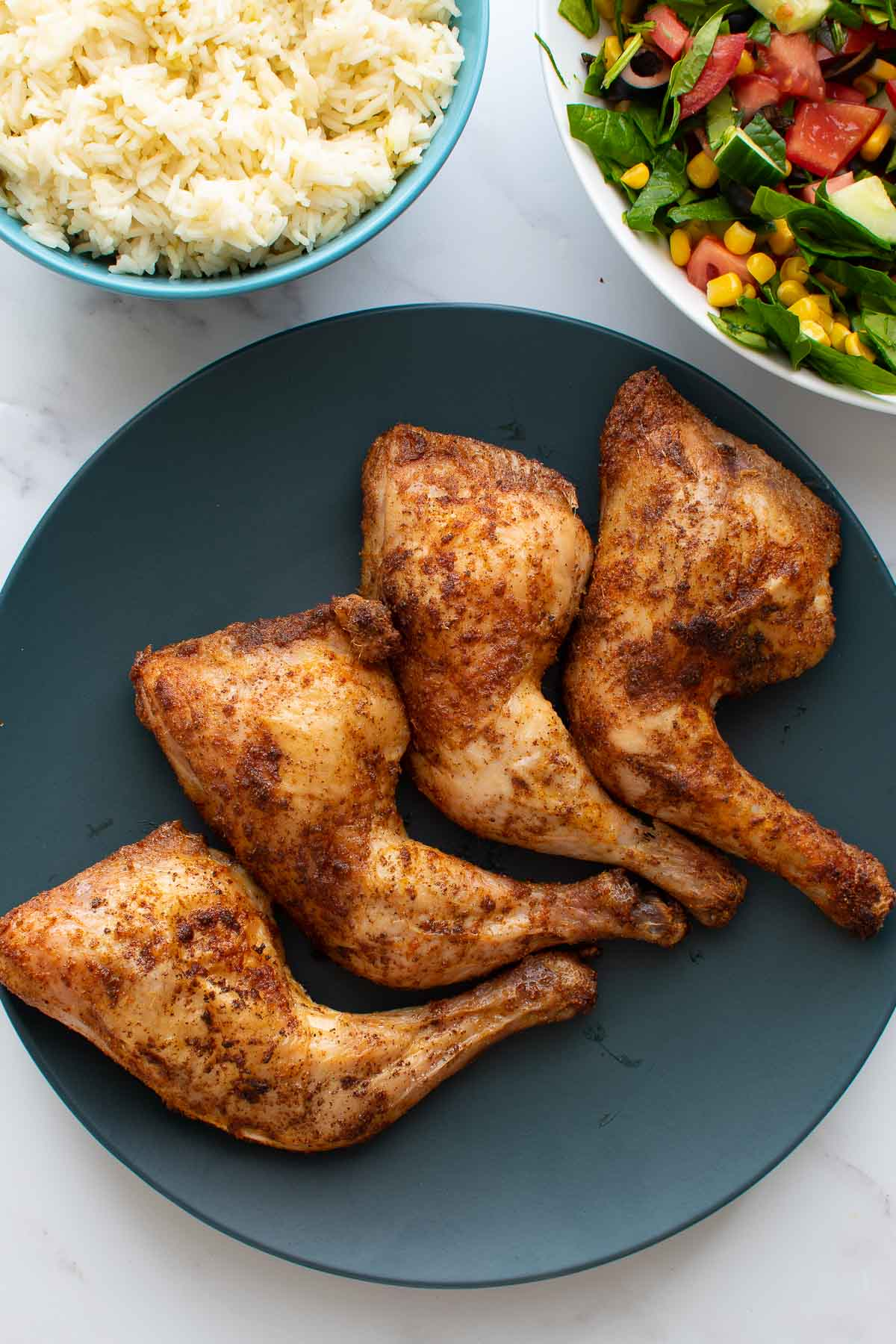 A plate of baked chicken leg quarters, with rice and salad on the side.