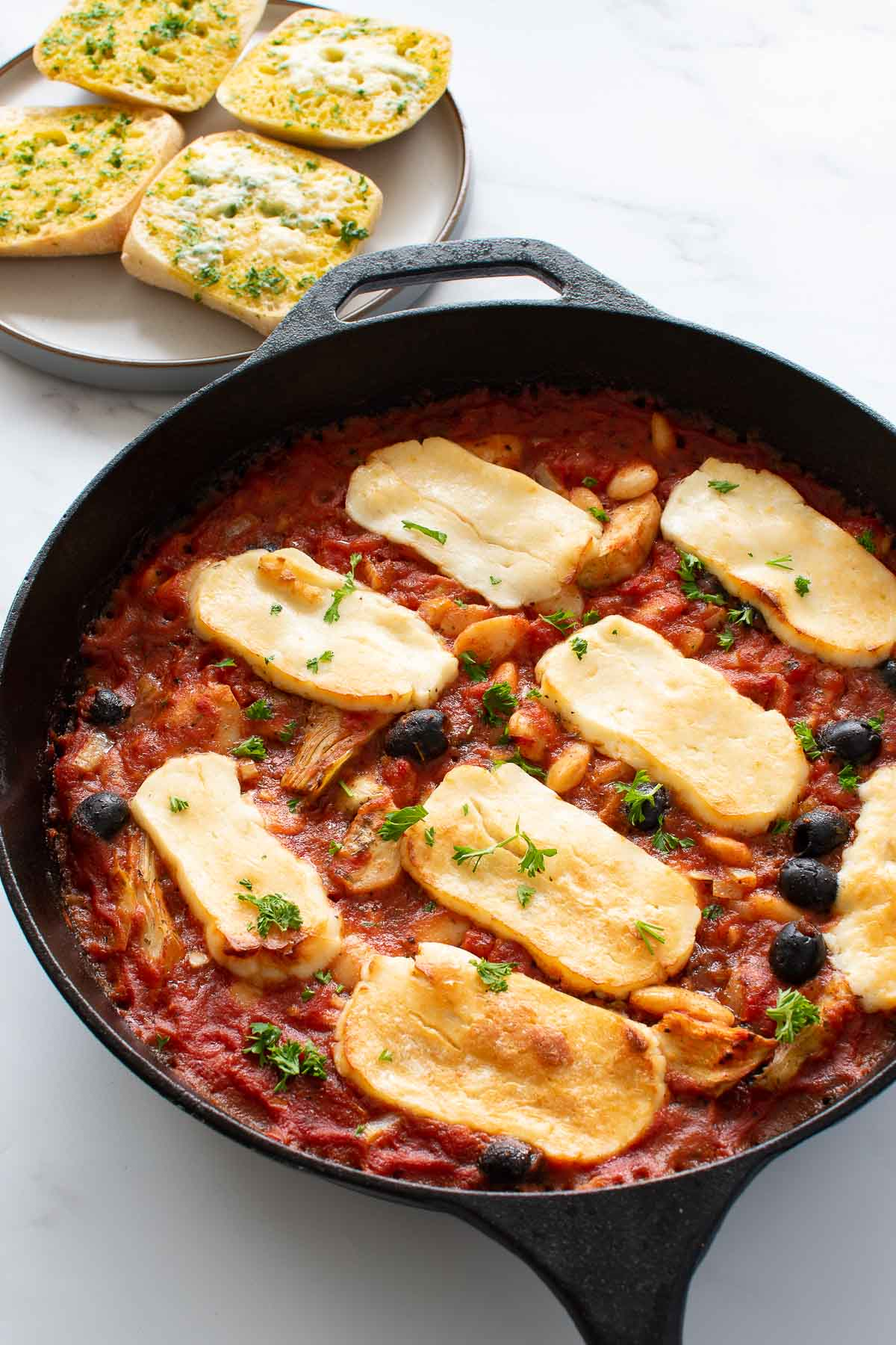 A pan with halloumi, tomato sauce, artichokes, butter beans and black olives.