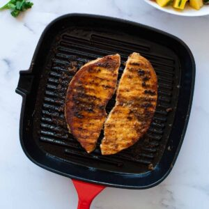 Two blackened swordfish fillets in a grill pan.